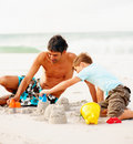 Father helping his son make sand castles Stock Images