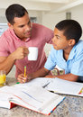 Father helping son with homework in kitchen Royalty Free Stock Photos