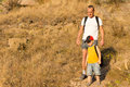 Father hiking with his small son descending a steep mountain trail wearing backpacks copyspace Stock Photography