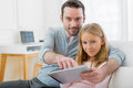 Father and his blond daughter using tablet view of a Stock Image