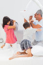 Father and his children fighting together with pillows on bed at home Royalty Free Stock Image