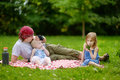 Father and his daughters picnicking in the park young Stock Images