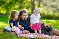 Father and his daughters picnicking in the park young Royalty Free Stock Photography