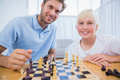 Father and his little boy playing chess in the living room Stock Photos