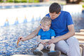 Father and his son by the fountain family of two floating a leaf boat Stock Photography