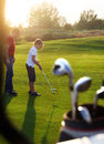 Father and his son playing golf together sunset Royalty Free Stock Images