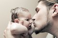 Father with his young baby cuddling and kissing him on cheek parenthood love Stock Photos