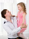 Father holding daughter and they dancing young happy beautiful little in his arms Royalty Free Stock Image