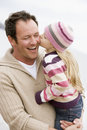 Father holding daughter kissing him at beach Royalty Free Stock Photo