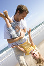 Father holding daughter upside down on beach Royalty Free Stock Photo