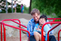 Father holding disabled son on merry go round at playground playing with child has cerebral palsy Stock Photography