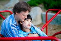 Father holding disabled son on merry go round at playground playing with child has cerebral palsy Royalty Free Stock Photo