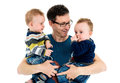Father is holding his twin sons in his arms. Royalty Free Stock Photo
