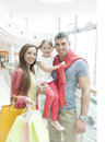 Father holding young girl posing with mother in shopping mall Royalty Free Stock Photography