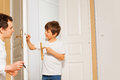 Father and kid son installing door handle together