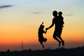 Father and kids jumping at sunset Royalty Free Stock Photo