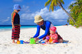 Father and kids making sand castle at tropical beach Stock Images