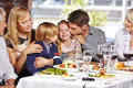 Father kissing daughter in restaurant while eating out with the family Royalty Free Stock Image