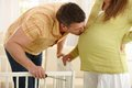 Father kissing mother s pregnant belly while fixing the bed for the baby at home Stock Images