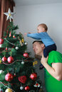 Father lift baby boy next to the Christmas tree Royalty Free Stock Photo