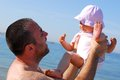 Father lifting his baby daughter on the beach loved months old healthy a sunny summer day Stock Photos