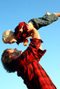 Father lifting son in air an attractive happy is his smiling little child up over his head with a blue summer sky the background Royalty Free Stock Photos