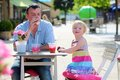 Father and little daughter drinking in cafe happy active men relaxing together with his adorable blonde toddler girl cozy outdoors Royalty Free Stock Photography