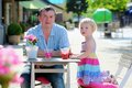 Father and little daughter drinking in cafe happy active men relaxing together with his adorable blonde toddler girl cozy outdoors Stock Images