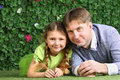 Father and little daughter lie on grass near hedge in garden Royalty Free Stock Photos