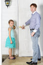 Father and little daughter stands near white entrance door of home focus on girl Royalty Free Stock Images