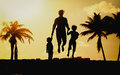 Father with little son and daughter jumping at sunset beach Royalty Free Stock Photo