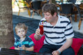 Father and little son sitting in cafe with cocktail on sunny sum summer day drinking Royalty Free Stock Images
