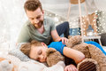 Father looking at cute little son sleeping with teddy bear Royalty Free Stock Photo