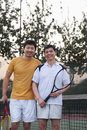 Father and mature son playing tennis, portrait Stock Photos