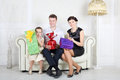 Father mother and daughter sit with bright gifts at white sofa in light room Royalty Free Stock Photography