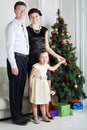 Father mother and daughter stand near christmas tree little cute in light room Stock Photography