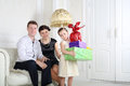 Father and mother sit at sofa and daughter with gifts white stands near their in light room Royalty Free Stock Photo