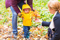 Father, mother and Son walking. Baby taking first steps with father help in autumn garden in the city Royalty Free Stock Photo