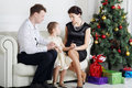Father and mother talk with daughter on sofa near christmas tree in light room Stock Image