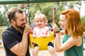 Father, mother with their daughter have fun on a swing Royalty Free Stock Photo