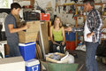 Father Organising Two Teenagers Clearing Garage For Yard Sale Royalty Free Stock Photo