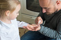 Father painting daughters finger nails Royalty Free Stock Photo
