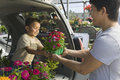 Father passing flower pot to son in back of a minivan at the plant nursery Royalty Free Stock Photo