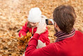 Father photograph his girl child playing in an autumn park man taking outdoor picture with mobile phone the Royalty Free Stock Images
