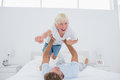 Father playing airplane holding his son in bed Royalty Free Stock Photos