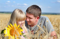 Father playing with his daughter in a wheat field cute small blond colorful yellow sunflower alongside they enjoy day nature Royalty Free Stock Image