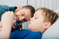Father playing with sick little boy lying in hospital bed, dad and son in hospital
