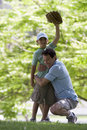 Father playing with son (10-12) in park, boy wearing baseball glove, hand raised, smiling, portrait