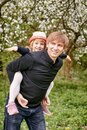 Father plays with his daughter in a flowering garden. Against the background of green grass and flowering trees