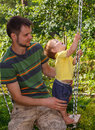 Father plays with his little son on the swing
